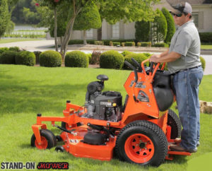 guy on a stand on mower