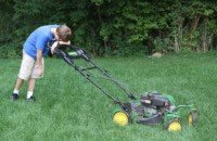 tired man mowing lawn with a walk-behind mower