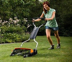 Young woman using a reel mower